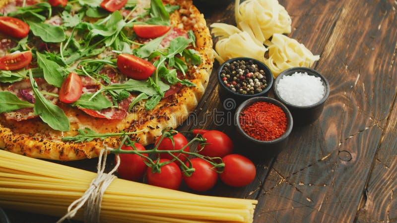 Italiaanse voedselachtergrond met pizza, ruwe deegwaren en groenten op houten lijst royalty-vrije stock afbeelding