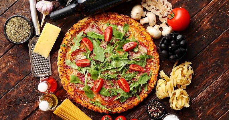 Italiaanse voedselachtergrond met pizza, ruwe deegwaren en groenten op houten lijst royalty-vrije stock afbeeldingen