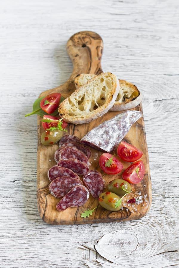 Italiaanse worst, broodciabatta, olijven en kersentomaten in olijfraad royalty-vrije stock foto's
