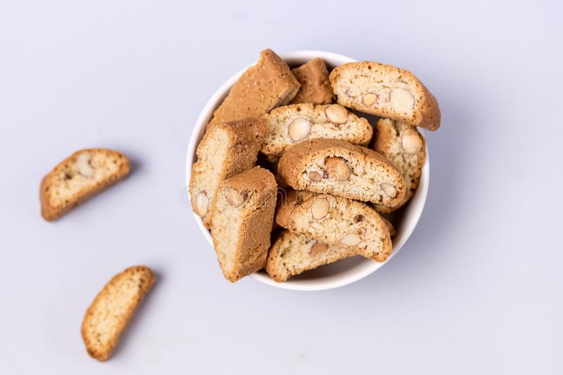 Italian Almond Biscuit Biscotti or Cantuccini in a White Bowl Tasty Italian Dessert for Coffee or Wine Top View Blue Background royalty free stock photo