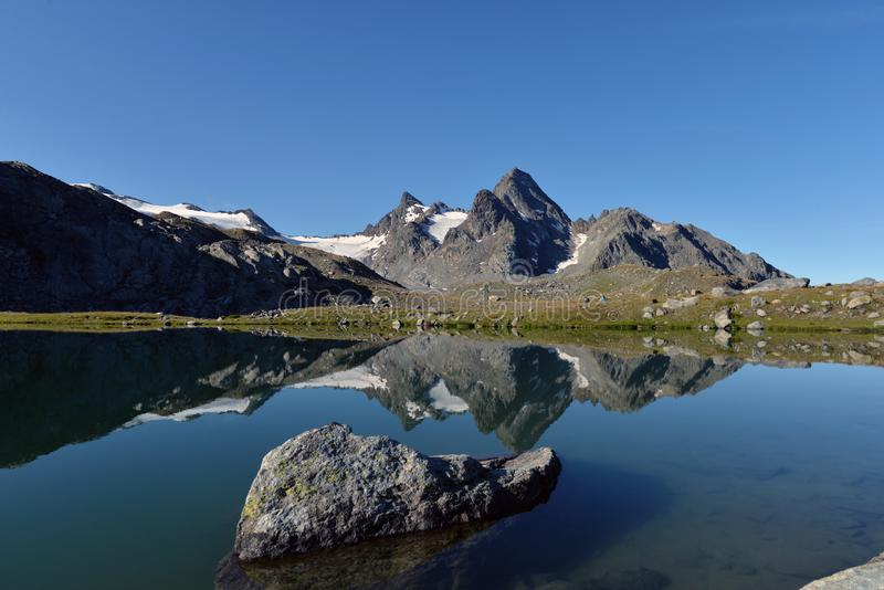 Italian alpine landscape and crystal clear lake reflecting the peaks. Dramatic mountain landscape in the Italian Alps, Aosta Valley region, Italy. Crystal clear royalty free stock photography