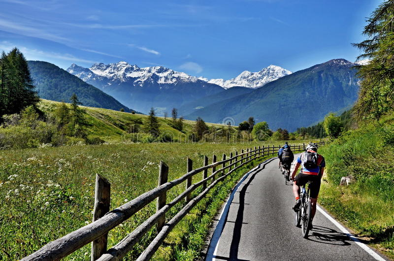 Italian Alps-unknown cyclists on the path. To Laders,in the foreground snowy peaks of the Dolomites royalty free stock photo