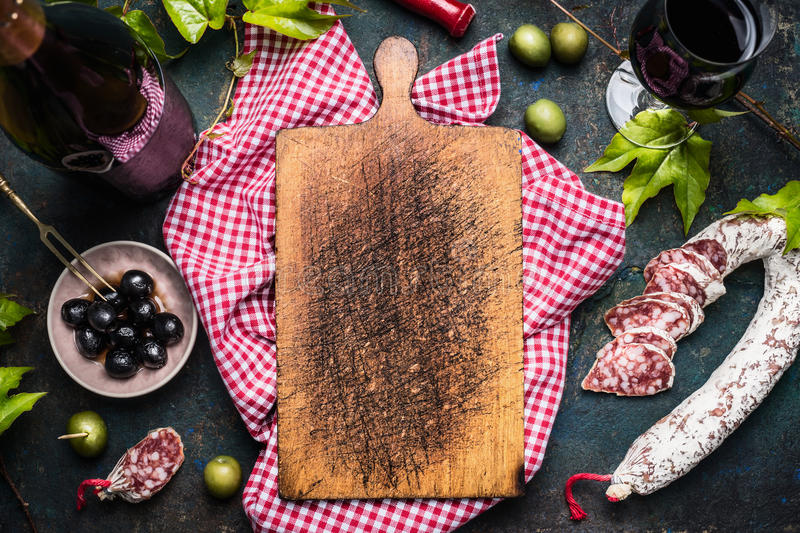 Italian antipasti with olives, red wine and salami around blank old cutting board, top view. Place for text. Italian food background royalty free stock image