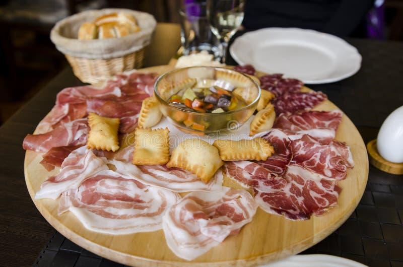 Italian antipasti. A serving of Italian antipasti, Parma ham, prosciutto, torta fritta, pickled vegetables and various meats stock photo
