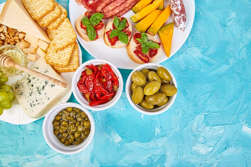 Italian antipasti wine snacks set. Antipasto catering platter. With jerky, salami, cheese , grapes, olives, pickles, Prosciutto di Parma with melon, Brushettas royalty free stock images