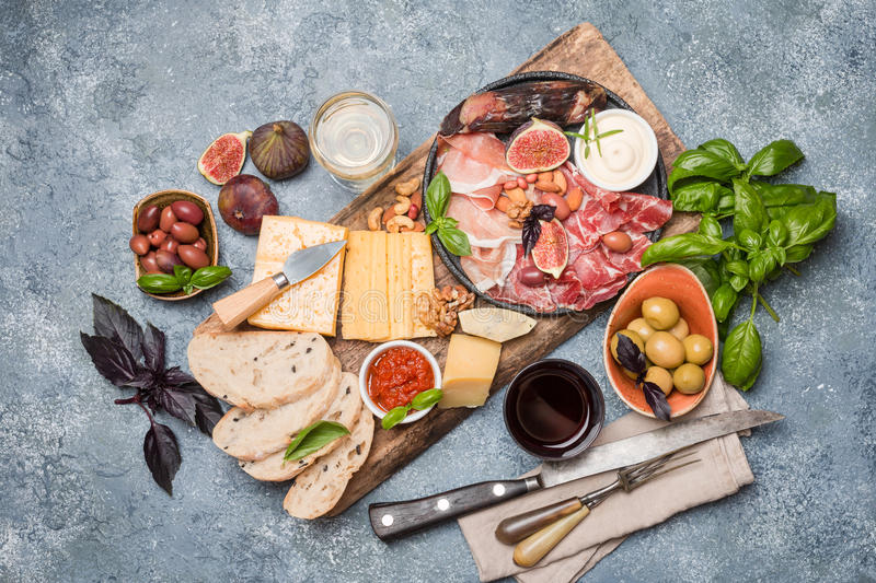 Italian antipasti wine snacks set. Cheese variety, nuts, Mediterranean olives, sauces, Prosciutto di Parma or jamon, and wine over gray background, top view stock photos