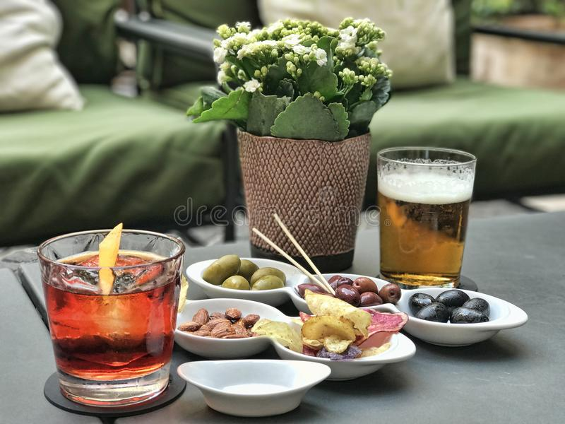 Italian antipasto with glasses of Americano and beer. Picture taken in Rome. The antipasto consists of green, red and black olives, almonds, and potato chips stock photo