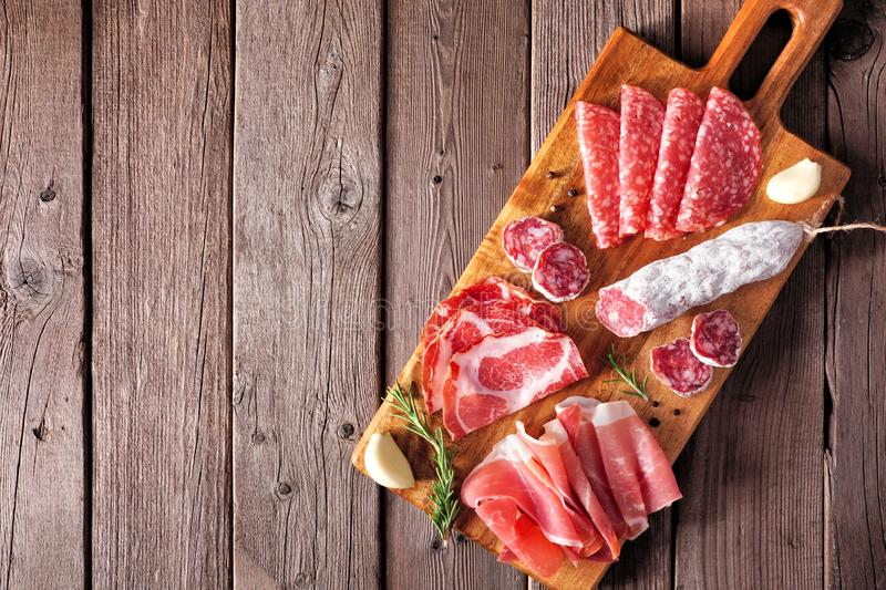 Italian antipasto meat platter with sausage, prosciutto, ham and salami, top view against a wood background stock photos