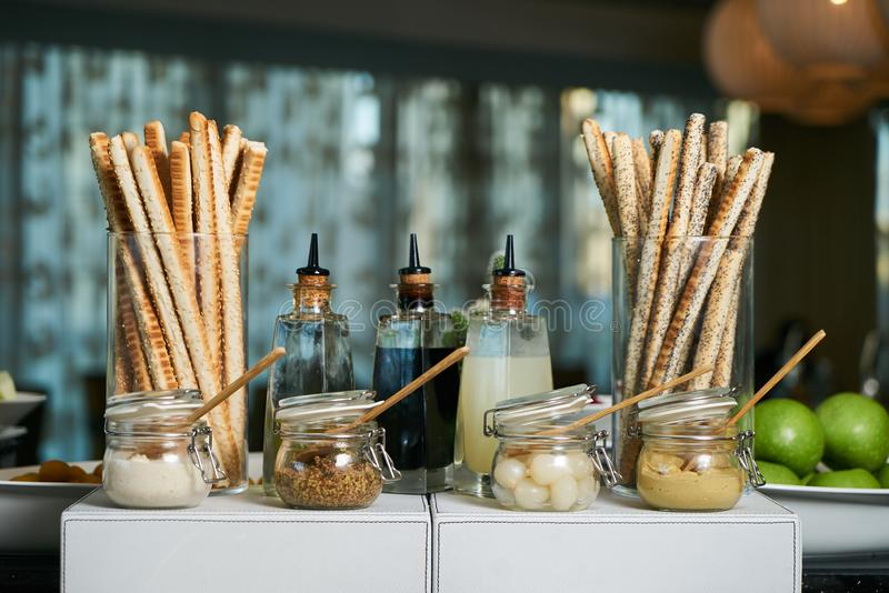 Italian Antipasto table setting with bread sticks and cheese. Crispy cheesy snack, bread - grissini and various types of cheese with sauces jars on restaurant stock photography
