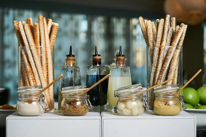 Italian Antipasto table setting with bread sticks and cheese. Crispy cheesy snack, bread - grissini and various types of cheese with sauces jars on restaurant royalty free stock photos