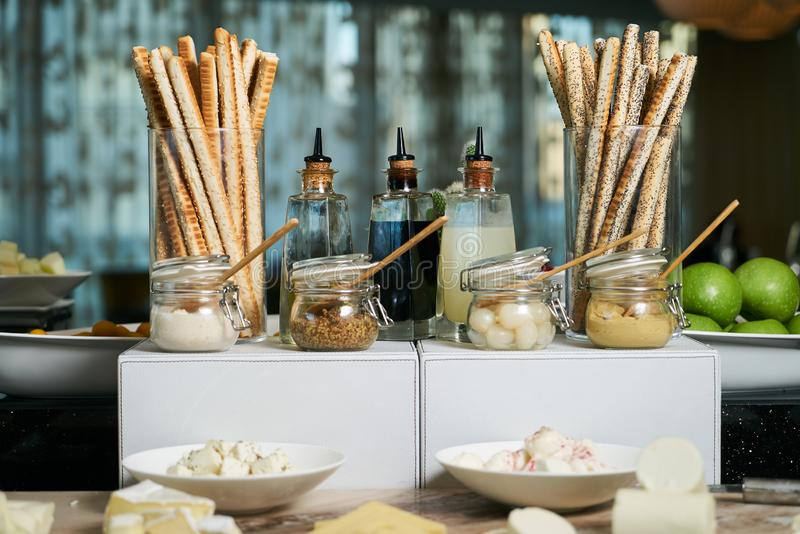 Italian Antipasto table setting with bread sticks and cheese. Crispy cheesy snack, bread - grissini and various types of cheese with sauces jars on restaurant stock images