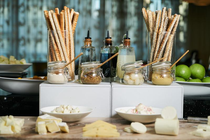 Italian Antipasto table setting with bread sticks and cheese. Crispy cheesy snack, bread - grissini and various types of cheese with sauces jars on restaurant royalty free stock photography