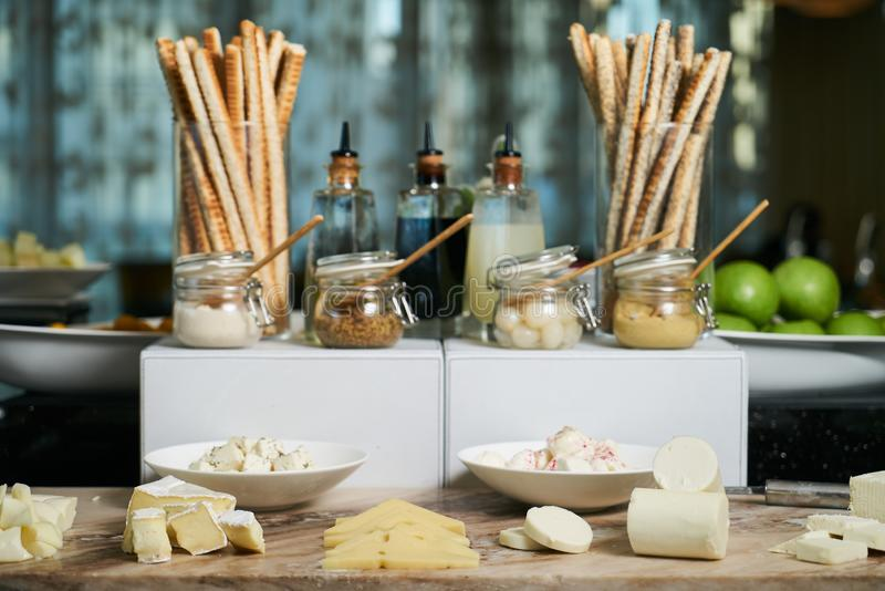 Italian Antipasto table setting with bread sticks and cheese. Crispy cheesy snack, bread - grissini and various types of cheese with sauces jars on restaurant royalty free stock images