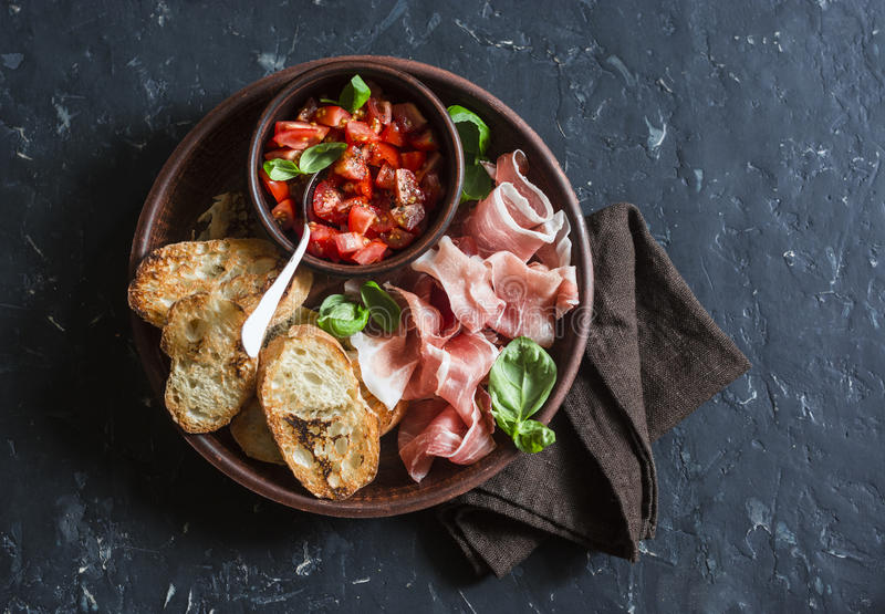 Italian antipasto - tomatoes bruschetta and prosciutto. On a dark background, top view. Delicious snack or appetizer. For wine stock photo