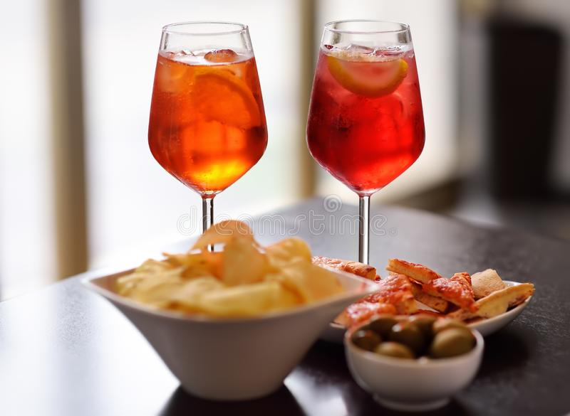 Italian aperitives/aperitif: glass of cocktail sparkling wine with Aperol and appetizer platter on the table. Traditional italian cuisine stock images