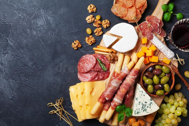 Italian appetizers or antipasto set with gourmet food on black kitchen table top view. Mixed delicatessen of cheese and meat snack royalty free stock images