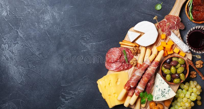 Italian appetizers or antipasto set with gourmet food on black stone table top view. Mixed delicatessen of cheese and meat snacks. royalty free stock photos
