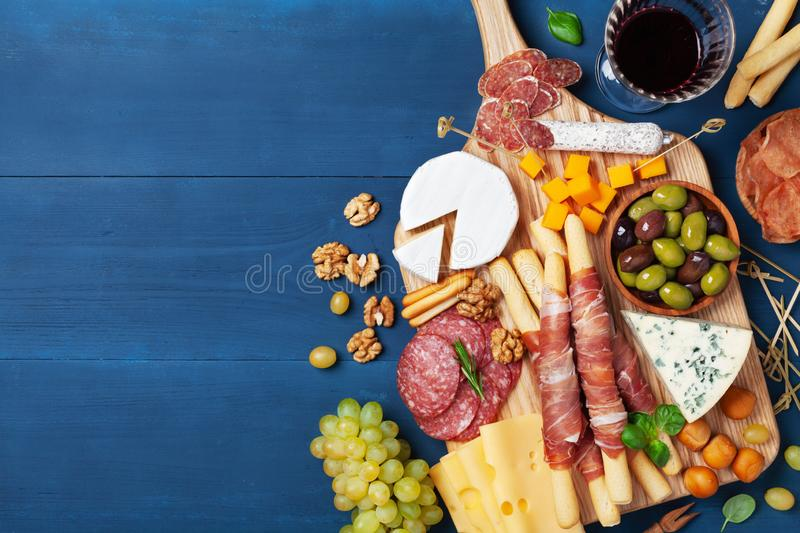 Italian appetizers or antipasto set with gourmet food on blue kitchen table top view. Mixed delicatessen of cheese and meat snacks. With red wine royalty free stock images