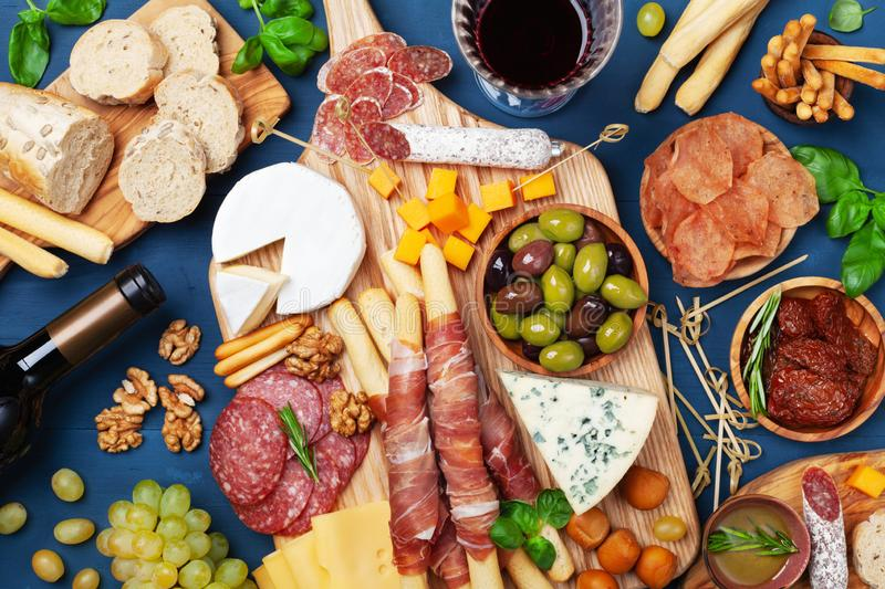 Italian appetizers or antipasto set with gourmet food on kitchen table top view. Mixed delicatessen of cheese and meat snacks stock photo