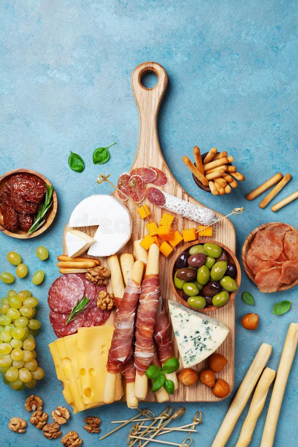 Italian appetizers or antipasto set with gourmet food on kitchen table top view. Delicatessen of cheese, olives and meat snacks. Italian appetizers or antipasto royalty free stock photos