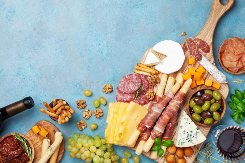Italian appetizers or antipasto set with gourmet food on table top view. Mixed delicatessen of cheese and meat snacks with wine royalty free stock images