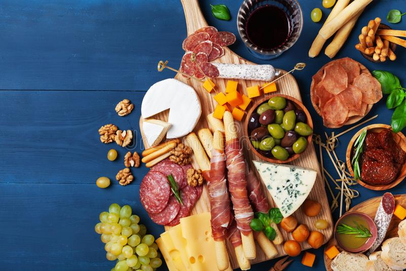 Italian appetizers or antipasto set with gourmet food on wooden kitchen table top view. Delicatessen of cheese and meat snacks royalty free stock photos