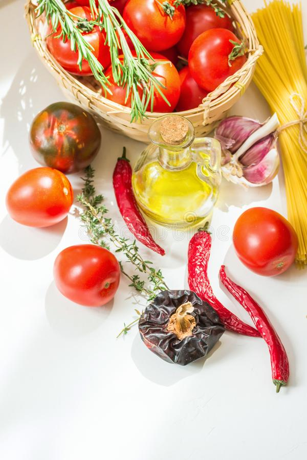 Free Italian Arrabiata Pasta Ingredients For Cooking. Spaghetti Tomatoes Hot Chili Peppers Culinary Herbs Olive Oil On White Table Stock Photography - 140592732