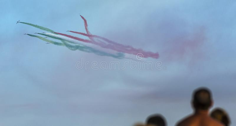 Planes jet with people looks at the italian tricolor arrows planes during an air show royalty free illustration