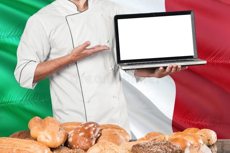 Italian Baker holding laptop on Italy flag and breads background. Chef wearing uniform pointing blank screen for copy space stock images