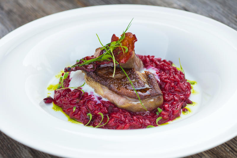 Italian beetroot risotto with delicious roasted duck breast royalty free stock photography