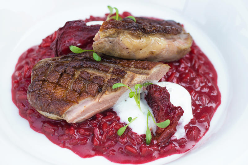 Italian beetroot risotto with delicious roasted duck breast royalty free stock image