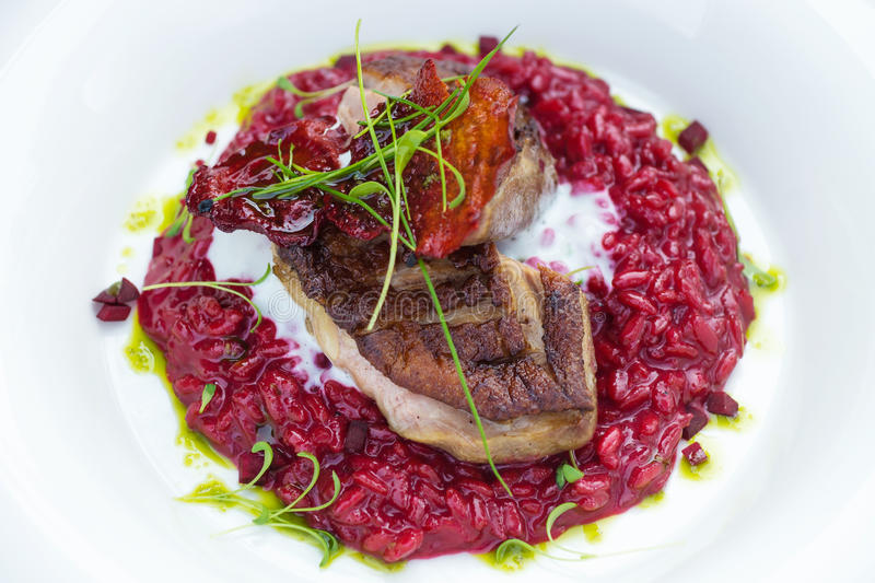 Italian beetroot risotto with delicious roasted duck breast royalty free stock photos