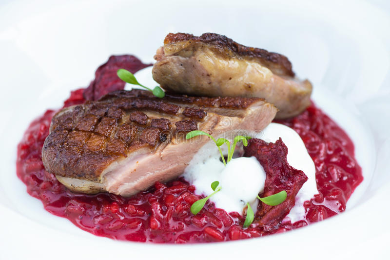 Italian beetroot risotto with delicious roasted duck breast stock image