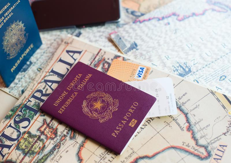An Italian and brasilian passports with a smartphone over a tourist magazine of South America and Australia, on a light background stock photography