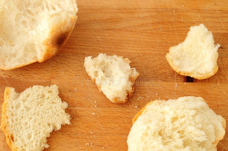 Italian bread, crumbs and bits. Breadcrumbs, and bits of broken bread on wooden background, high angle view stock image