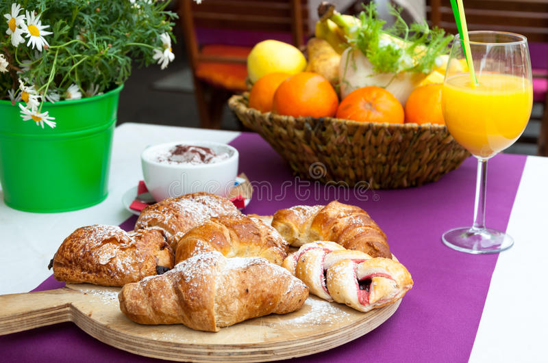 Italian breakfast in cafe. Table with italian breakfast served in cafe - croissants, fesh orange juice and coffee stock photo