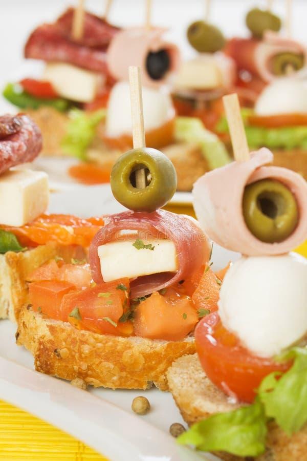 Italian bruschetta canape. Italian bruschetta bread with ham, cheese, tomato and olives stock images