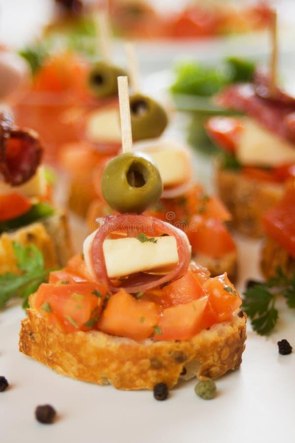 Italian bruschetta canape. With olive, prosciutto, cheese and tomato stock images