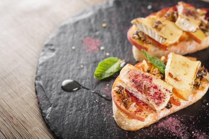 Italian bruschetta with cheese brie, camembert and peach. Tasty italian bruschetta with cheese brie, camembert and peach at a cafe table royalty free stock photo