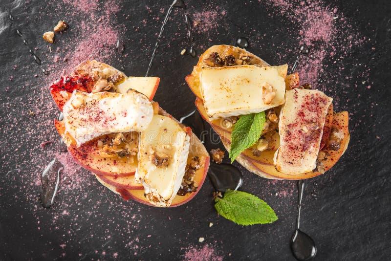 Italian bruschetta with cheese brie, camembert and peach. Tasty italian bruschetta with cheese brie, camembert and peach at a cafe table. Top view stock photos