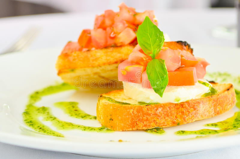 Italian Bruschetta with cheese tomatoes and a basil dressing stock photos