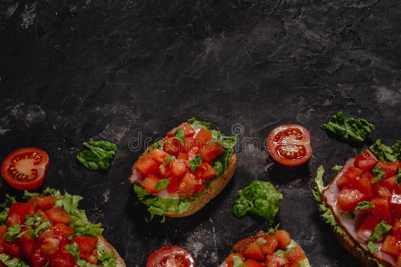 Italian Bruschetta with chopped tomatoes, mozzarella sauce and salad leaves. Traditional italian appetizer or snack, antipasto. stock image