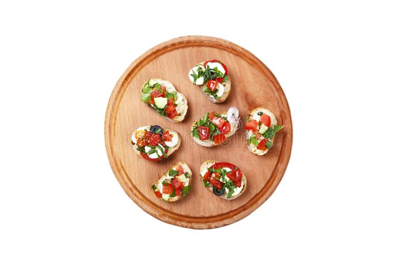 Italian bruschetta with fried tomatoes, mozzarella cheese and greens on a cutting board on a white background royalty free stock image