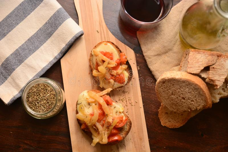 Italian bruschetta toasted with tomato mozzarella cheese origan aubergine under oil tipic gourmet food. Cuisine italy snack appetizer on wood table royalty free stock photos