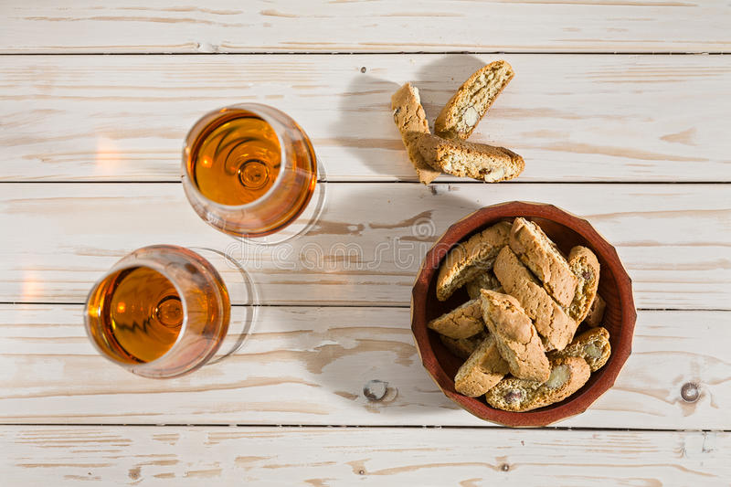 Italian cantucci biscuits and two glasses of vin santo wine. On a table seen from above royalty free stock images
