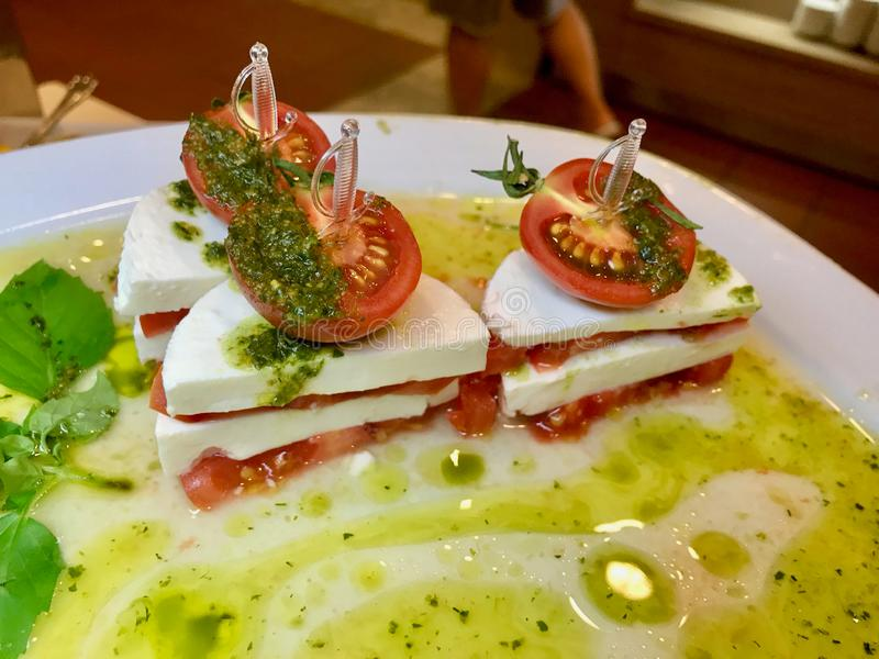 Italian Caprese Salad as Appetizer with Olive Oil, Mozzarella Cheese and Sliced Tomato Slice with Food Skewers stock photos