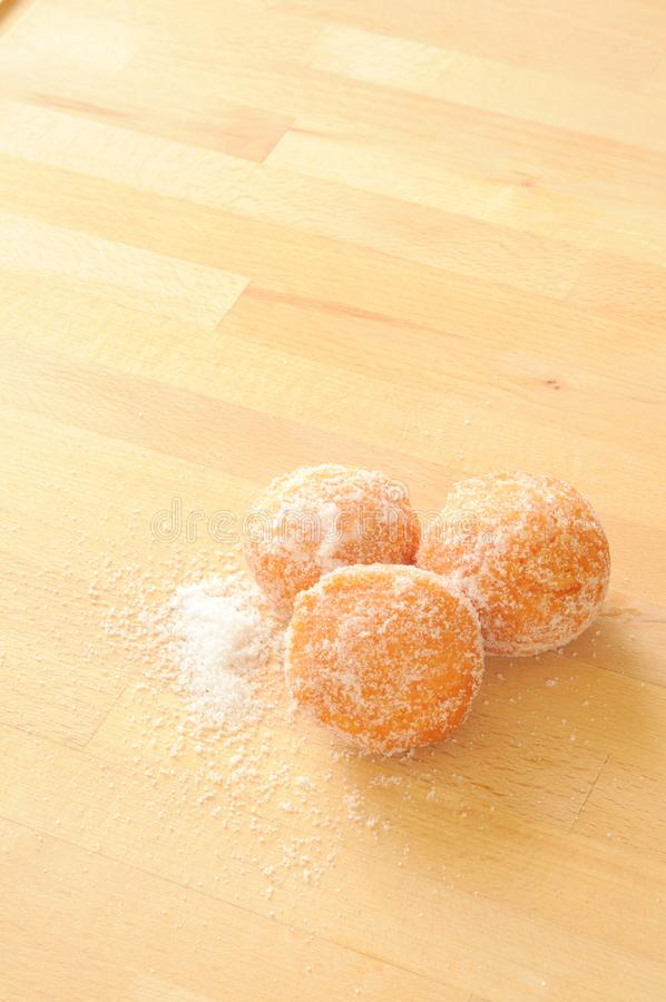 Italian Carnival sweet fried. Three sweet fritters, surrander by granulated sugar, fired typical in Italy on Carnival, vertical frame stock photo