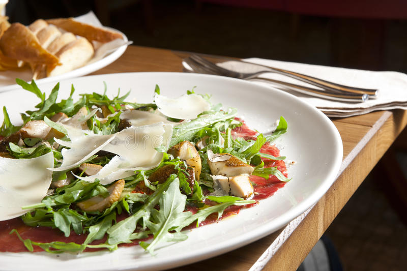 Italian carpaccio on restaurant table. With fork and knife royalty free stock photography