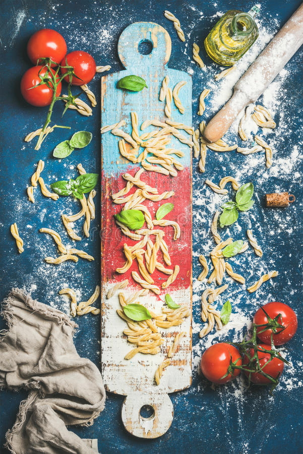 Italian casarecce, cherry-tomatoes, basil leaves and olive oil on board royalty free stock photos