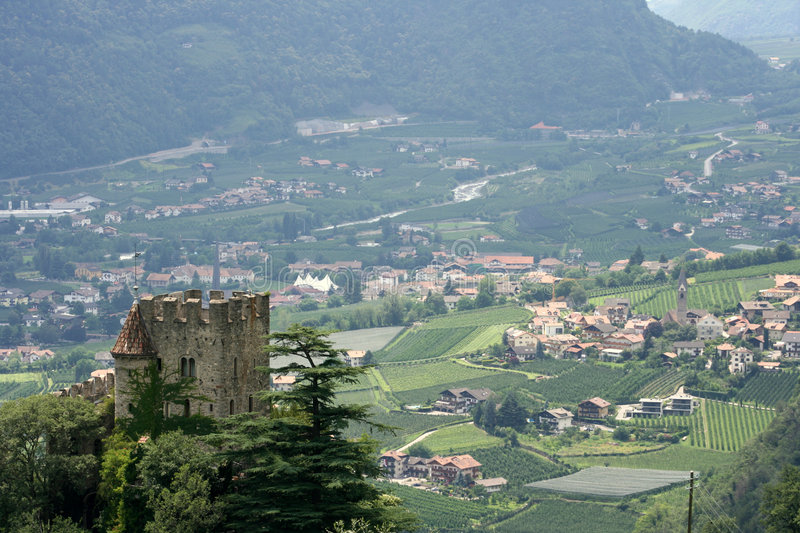 Italian castle in countryside. Aerial view of historical castle in countryside with mountain in background, Meran, South Tirol, Italy royalty free stock photo